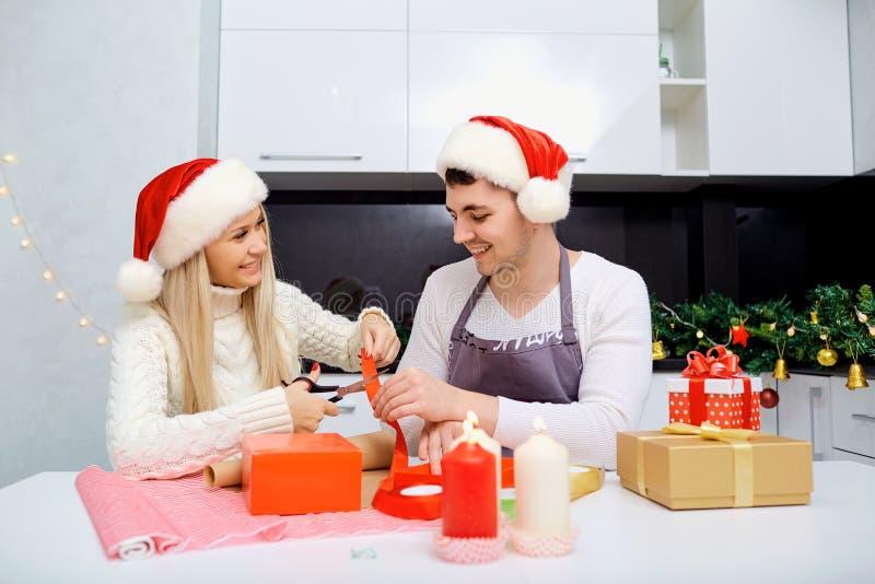 Una coppia nel ` s di Santa ricopre lo spostamento dei presente in una stanza su Christma fotografia stock