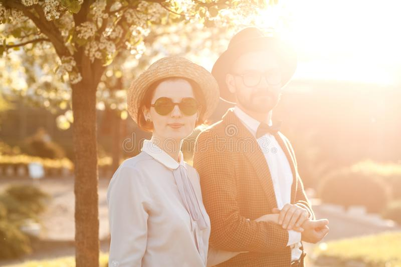 Una coppia nell'amore al tramonto in cappelli sta con le loro parti posteriori in Th fotografia stock