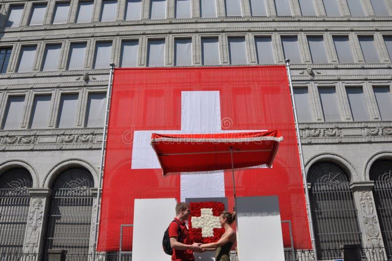 Una coppia nell'amore davanti alla bandiera svizzera enorme al cittadino di tha immagine stock