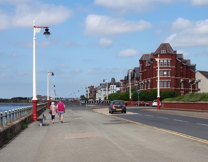 Una coppia più anziana che cammina per la marina nel sud merseyside con vecchi edifici alberghieri in fila per la strada in una b immagini stock libere da diritti