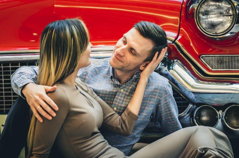Una coppia romantica sta sedendosi vicino all'automobile rossa Un uomo sta abbracciando una donna Classici americani Il tipo e la fotografia stock libera da diritti