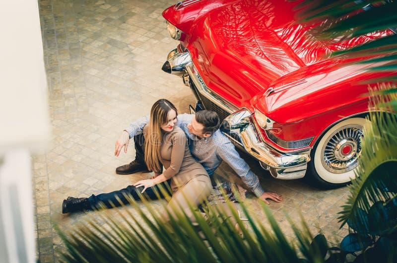 Una coppia romantica sta sedendosi vicino all'automobile rossa Un uomo sta abbracciando una donna Classici americani Il tipo e la fotografia stock