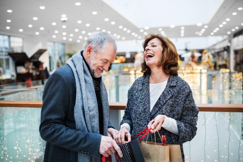 Una coppia senior con i sacchi di carta nel centro commerciale a tempo di Natale fotografia stock