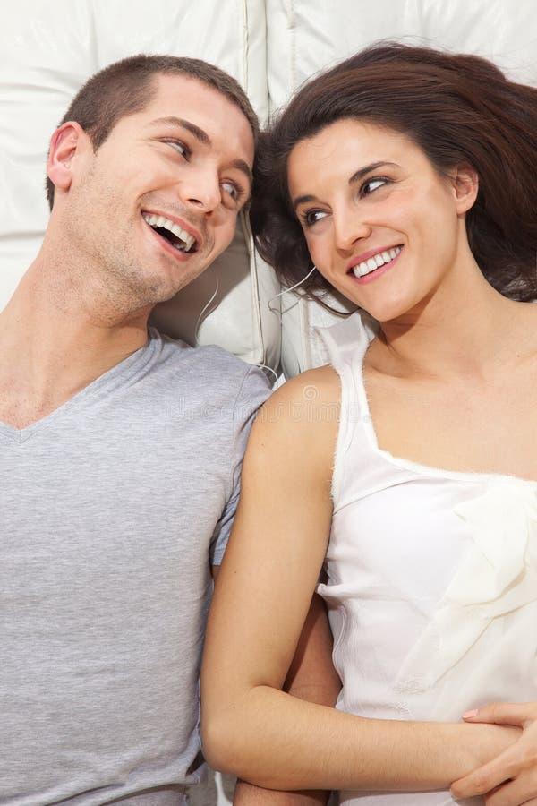 Giovani coppie adorabili che si trovano insieme in un letto ed in una musica listenning immagini stock