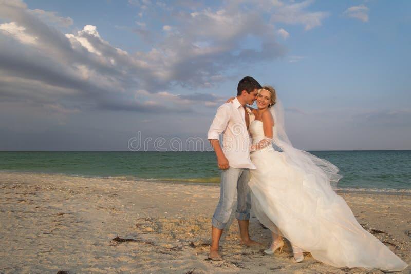 Una coppia sposata che cammina sulla spiaggia immagine stock
