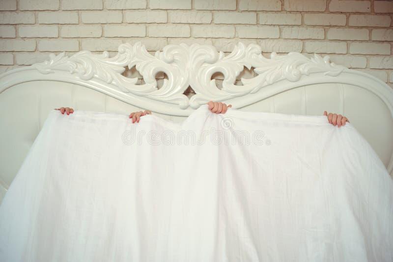 Una coppia sposata divertente, trovantesi a letto e nascondentesi sotto una coperta bianca, soltanto armi è visibile Divertimento fotografia stock libera da diritti