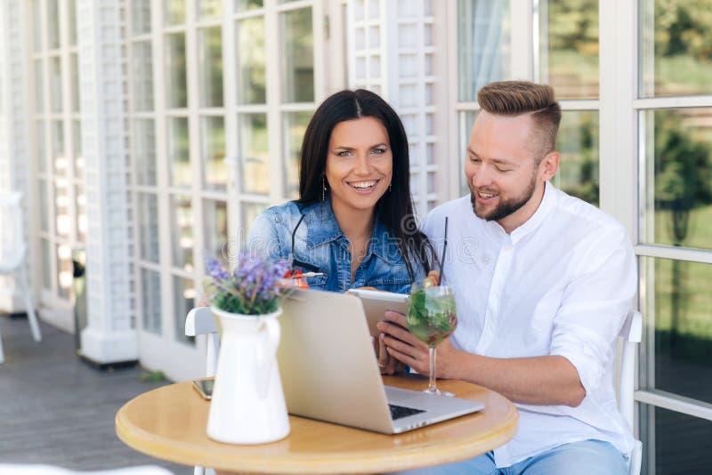 Una coppia sposata felice sta riposando in un caffè, ridendo, godente dei cocktail deliziosi, facendo uso degli smartphones e di  immagini stock