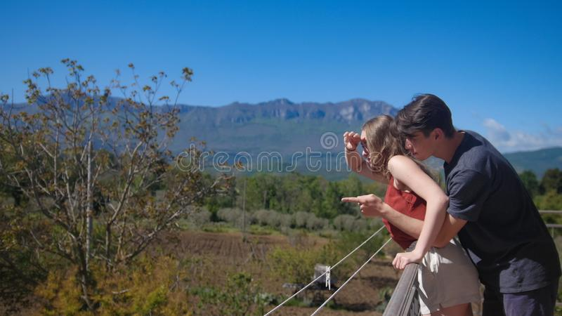 Una coppia sta stando sull'abbraccio del balcone Consideri il paesaggio degli alberi fotografie stock libere da diritti