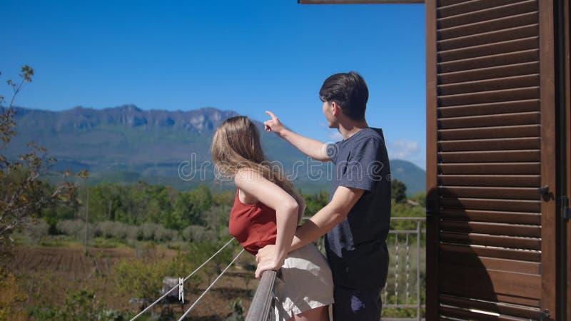 Una coppia sta stando sull'abbraccio del balcone Consideri il paesaggio della montagna fotografia stock libera da diritti