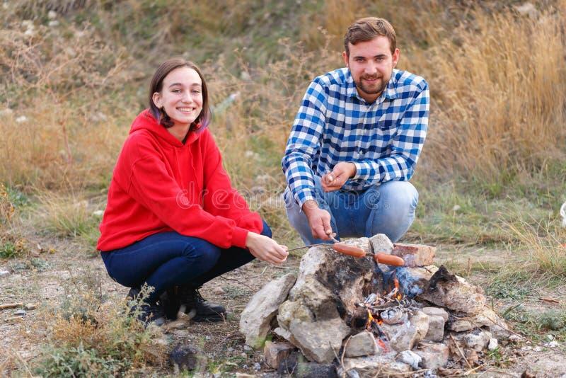 Una coppia su un picnic frigge le salsiccie appetitose all'aperto fotografie stock