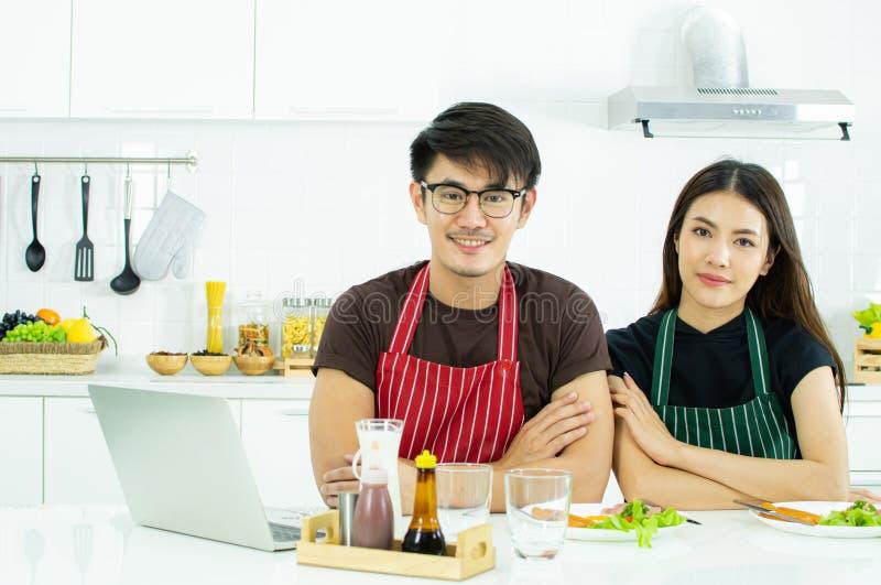 Una coppia sveglia sta sedendosi nella cucina moderna fotografia stock libera da diritti