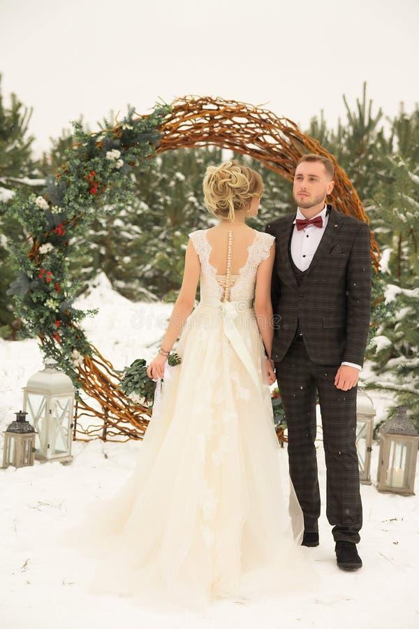 una coppia un uomo e una donna sta stando contro lo sfondo di una foresta dell'inverno, un cerchio dei fiori decorati con le viti fotografia stock