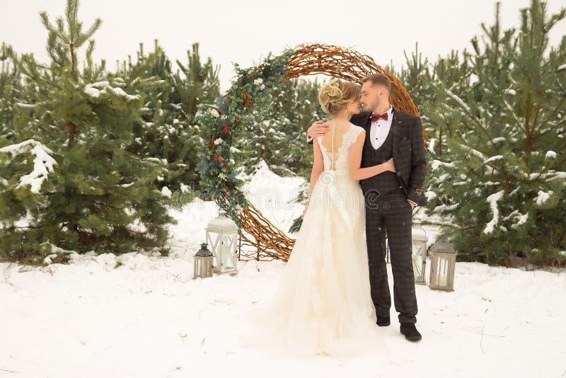 una coppia un uomo e una donna sta stando contro lo sfondo di una foresta dell'inverno, un cerchio dei fiori decorati con le viti fotografia stock libera da diritti