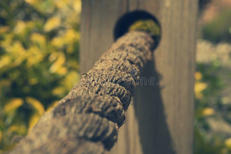 Una corda bianca legata ad un recinto di legno ad un giardino immagini stock