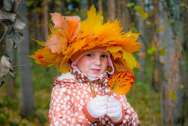 Una corona da giallo va sulla testa della ragazza Ritratto di autunno di una bambina che indossa una corona delle foglie gialle fotografia stock
