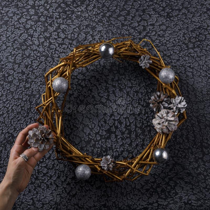 Una corona dei rami dipinti in oro e decorati per il nuovo anno su un fondo nero Lavoro manuale quadrato fotografie stock