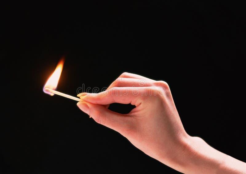 Una corrispondenza burning in una mano immagine stock libera da diritti