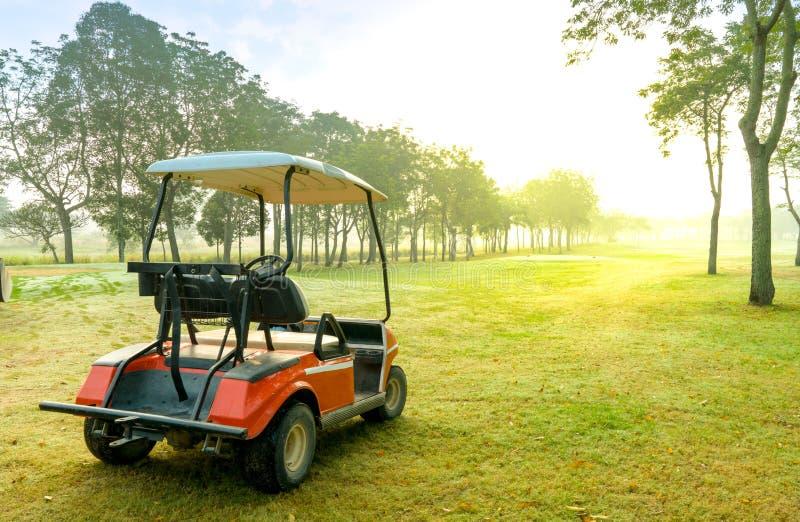 Una corte y un carro del golf del VERDE LARGO por la mañana con luz del sol foto de archivo libre de regalías