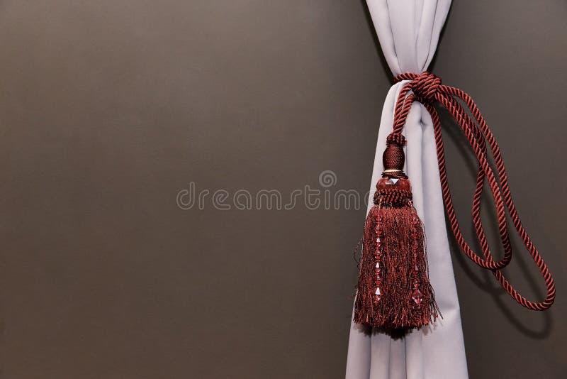 Una cortina ligera recolectó por una cuerda roja con las franjas y las piedras contra la perspectiva de un de un sólo recinto imágenes de archivo libres de regalías