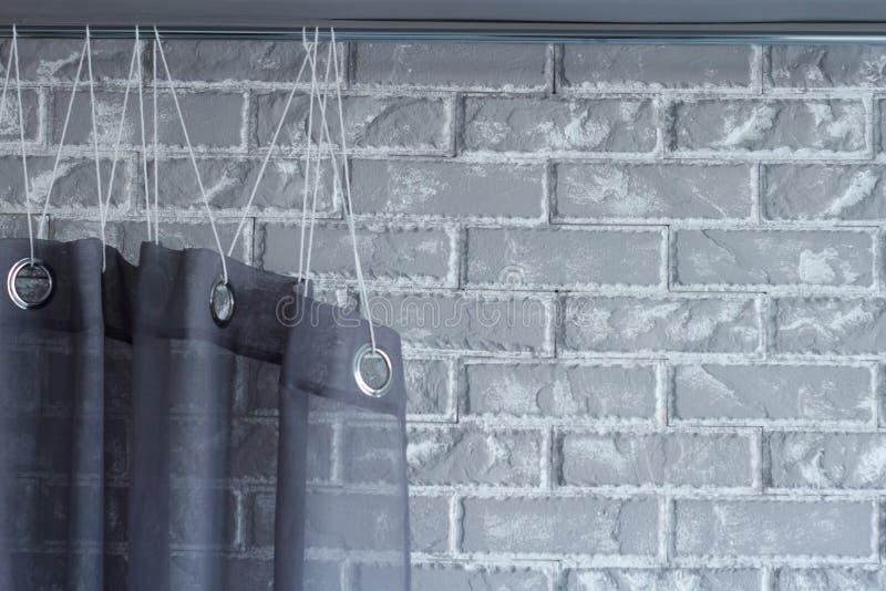 Una cortina negra cuelga de Cornualles en el fondo de una pared de ladrillo gris, el fondo o el concepto foto de archivo libre de regalías