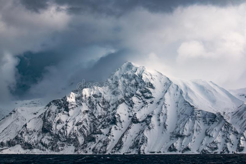 Una costa rocciosa di una delle isole di Kuril nell'inverno durante la tempesta della neve immagine stock libera da diritti