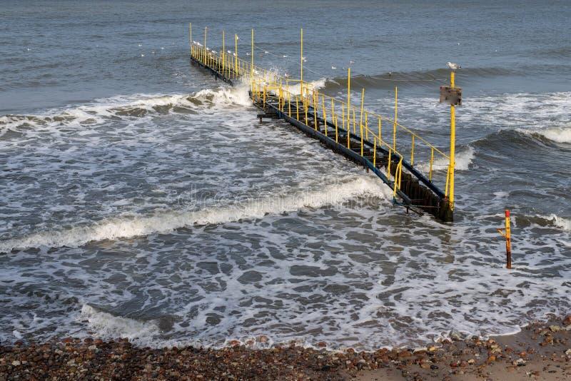 Una costruzione metallica sopra il Mar Baltico ruvido Ponte sulla costa immagini stock