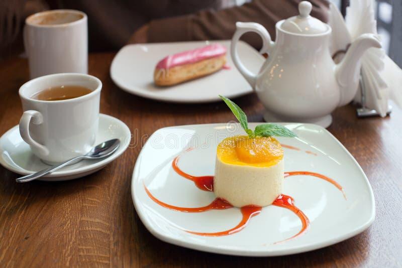 Una crema batida con el atasco del passionfruit con el jarabe y el té rojos foto de archivo