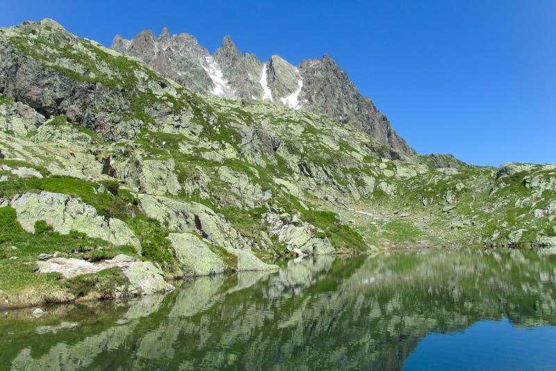Una cresta delle montagne rocciose e del lago nelle alpi immagine stock libera da diritti