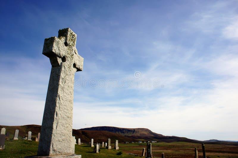 Una croce celtica del cimitero tra altre tombe fotografia stock