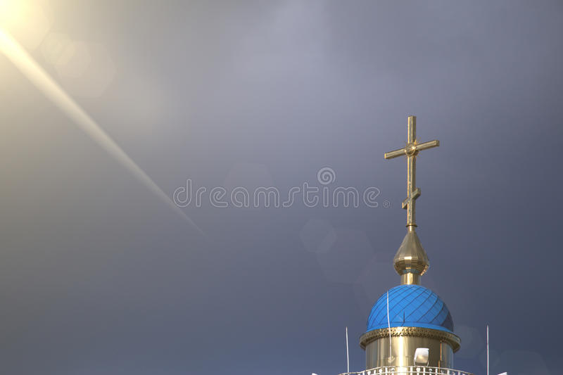 Una cruz cristiana grande en la cual cae un rayo del sol a través de las nubes fotos de archivo