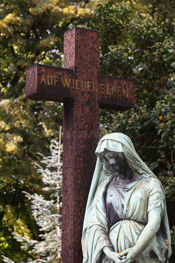 Una cruz y un ángel en un cementerio fotos de archivo libres de regalías
