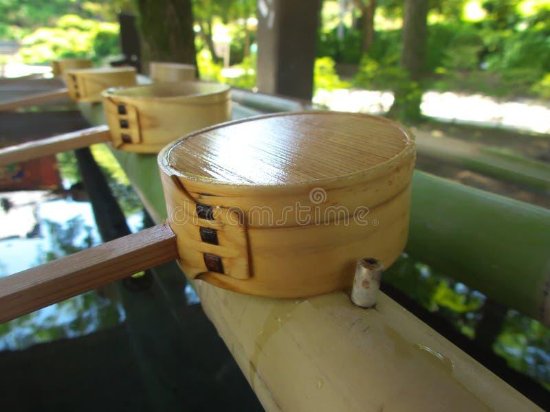 Una cucharón o un cazo para purificar sus manos y boca en el chozuya en una capilla sintoísta imagen de archivo