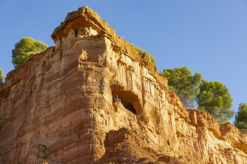Una cueva con una silla en la montaña - escarpa sobre Anento fotografía de archivo