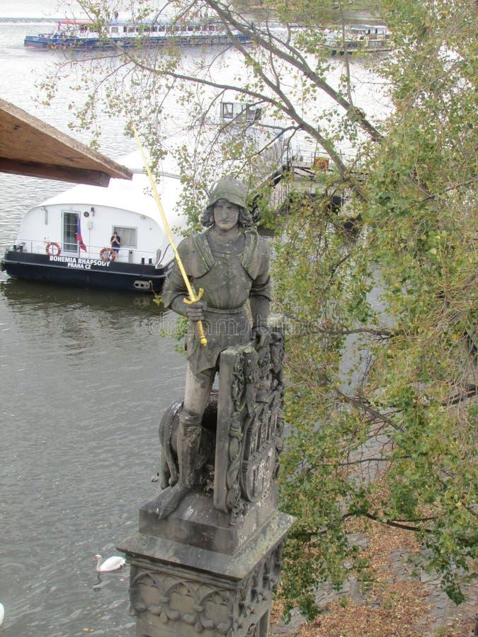 Una de las figuras esculturales en Charles Bridge legendario a través del río de Moldava en Praga, República Checa imágenes de archivo libres de regalías