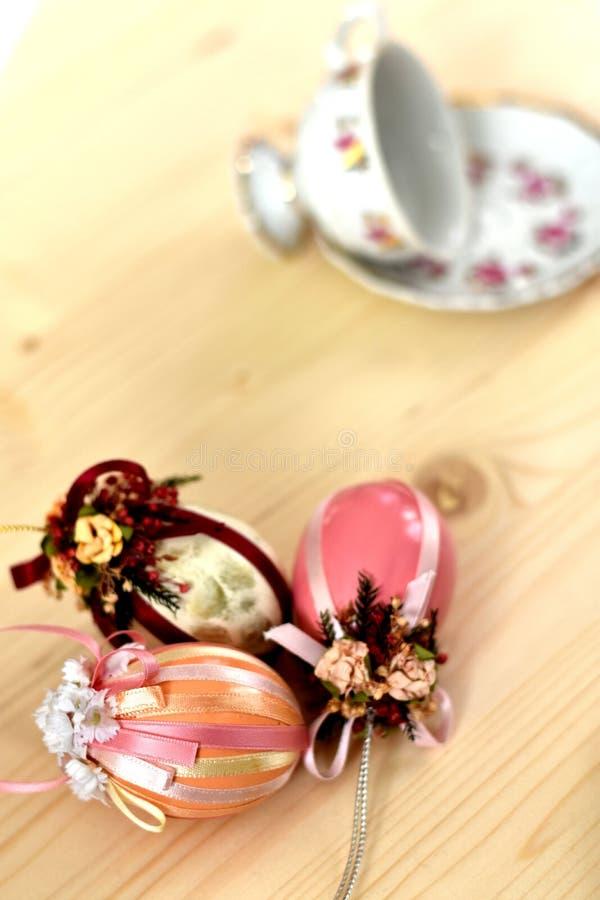 Una decorazione d'annata di Pasqua di tre uova di Pasqua colorate rosa brillanti decorate con i nastri e tazza d'annata e piattin fotografia stock libera da diritti