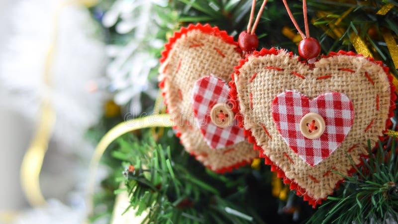 Una decorazione di Natale di due cuori contro lo sfondo di un albero di Natale fotografie stock