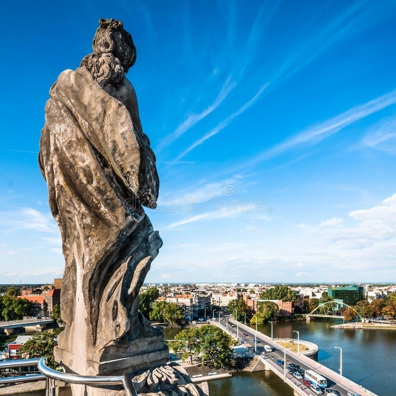 Una di quattro statue sul tetto di Wroclaw Universit fotografia stock