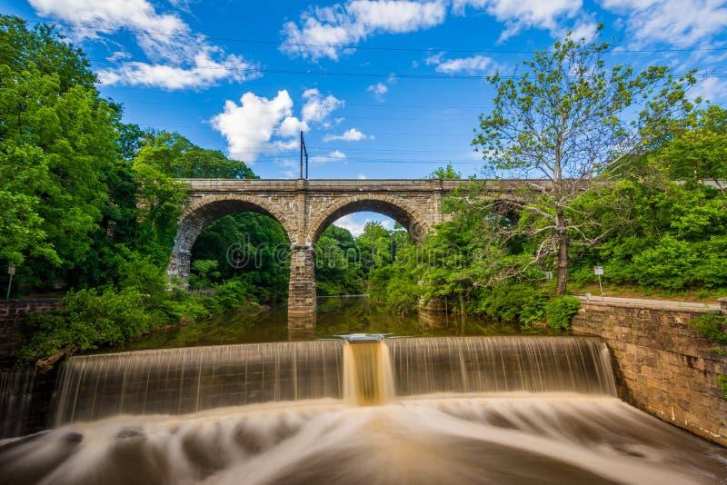 Una diga sull'insenatura di Wissahickon e sul vecchio ponte della ferrovia, in Filadelfia, la Pensilvania fotografia stock libera da diritti