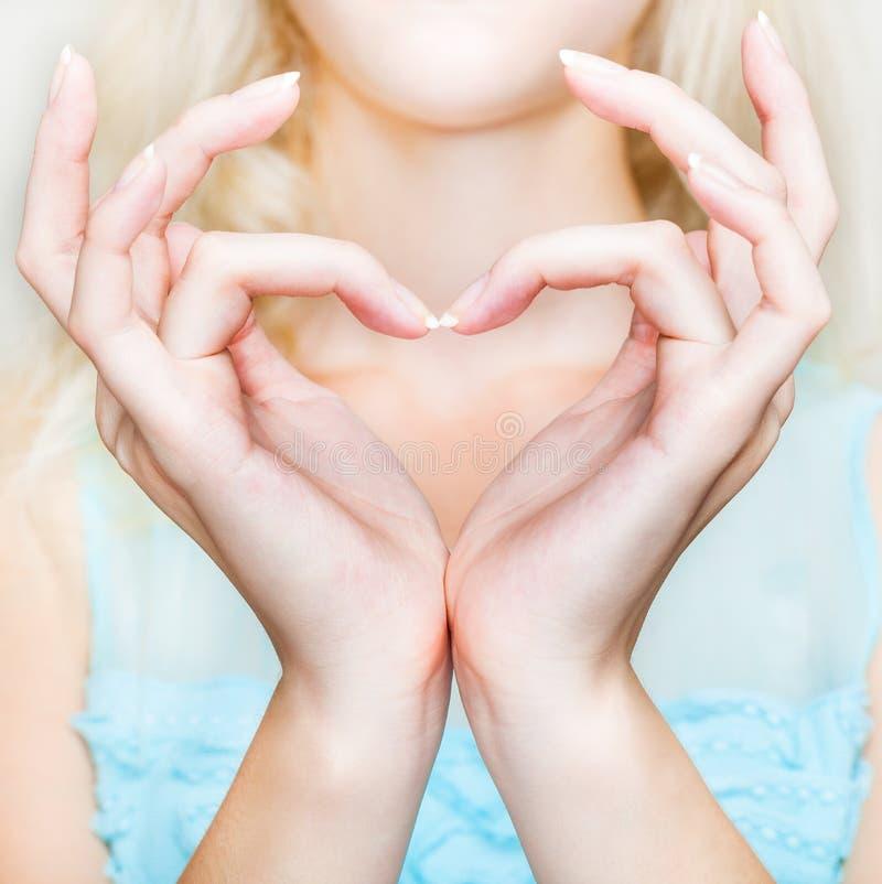Una dimensión de una variable del corazón se hace de dos palmas foto de archivo libre de regalías