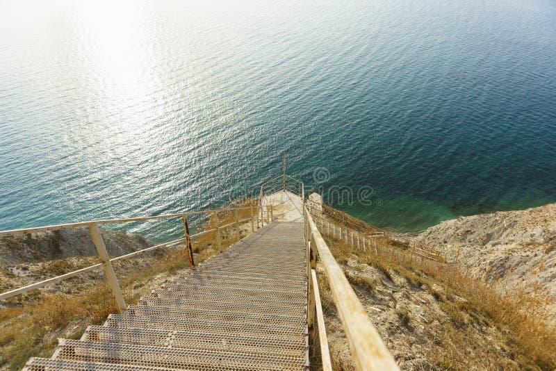Una discesa ripida giù le scale lunghe del metallo alla riva del mare blu fotografia stock