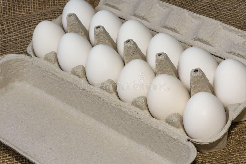 Una docena de huevos blancos contra un fondo de huevos de gallina burlap, 18 de abril de 2020 foto de archivo libre de regalías