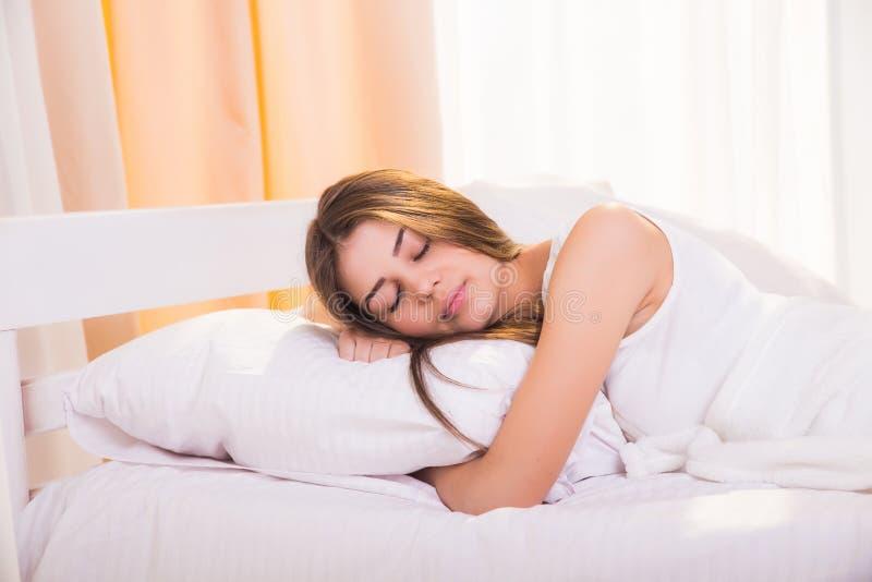 Una donna addormentata sta trovandosi a letto con la sua testa fotografia stock