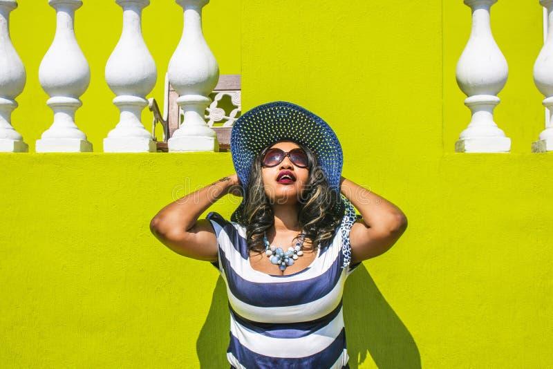 Una donna africana bella in un vestito a strisce blu e bianco che modella davanti ad una casa tradizionale BO-Kaap con la parete  fotografia stock libera da diritti