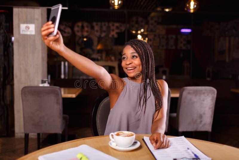 Una donna afroamericana sta prendendo il selfie fotografia stock libera da diritti