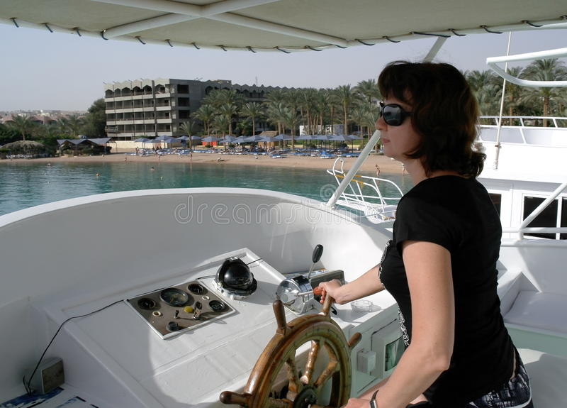 Una donna al timone di un yacht immagine stock