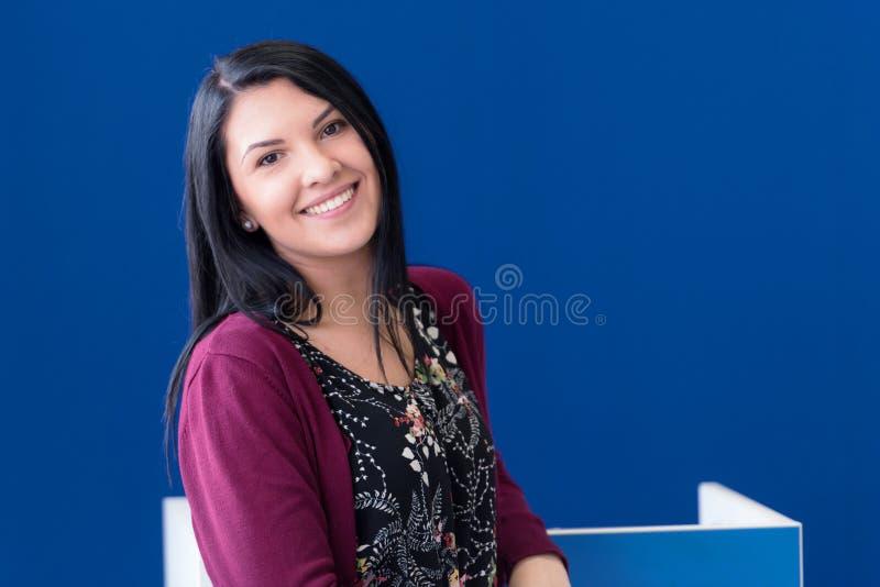 Una donna allegra e allegra, con i capelli neri, vestita casualmente, guardando con soddisfazione la telecamera, essendo felice immagine stock