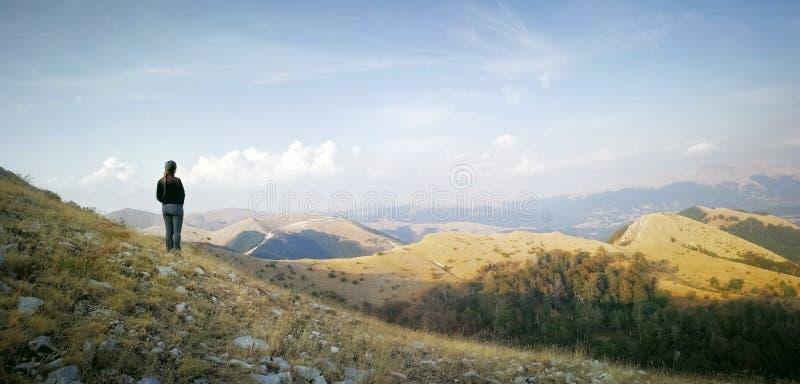 Una donna ammira il paesaggio dell'estate da una cima della montagna, in fotografie stock libere da diritti
