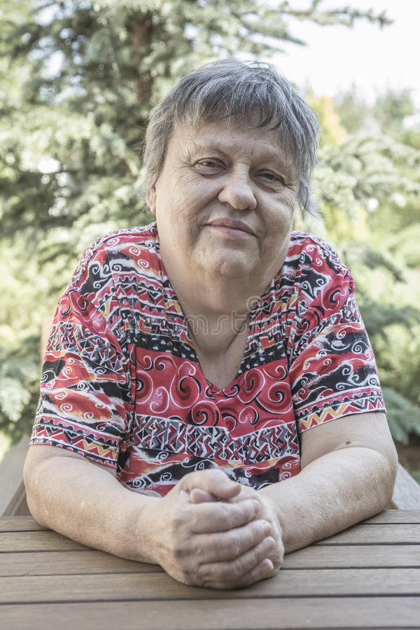 Una donna anziana adorabile che si siede al giardino immagine stock