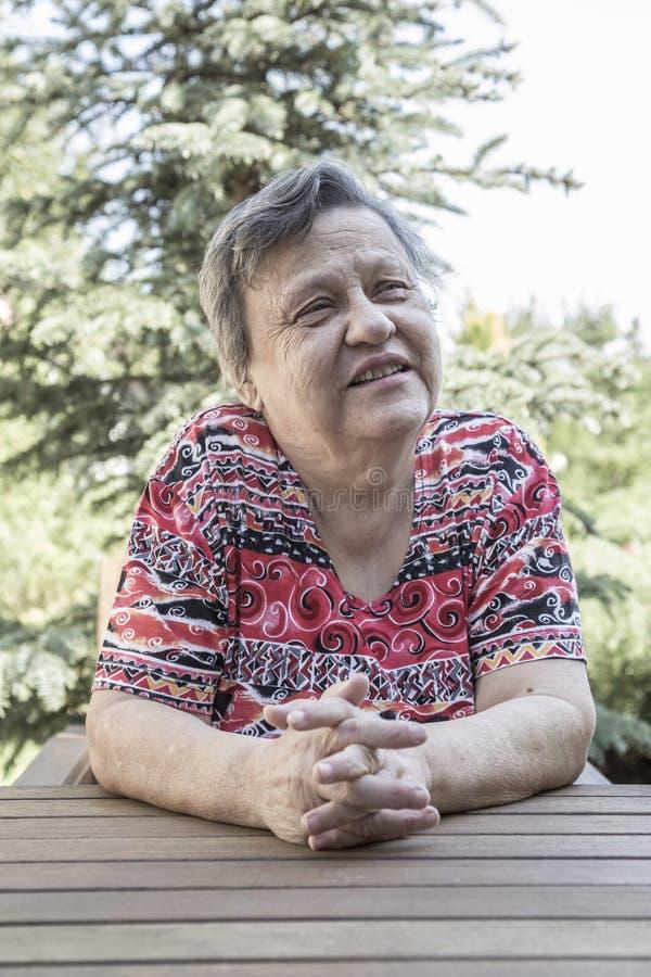 Una donna anziana adorabile che si siede e che parla al giardino immagine stock libera da diritti