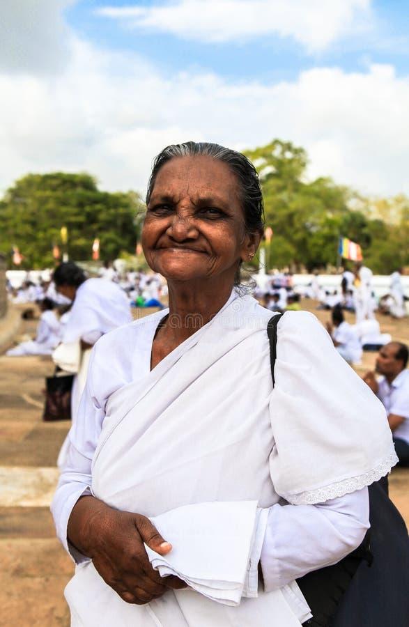 Una donna anziana ai pellegrini in Anuradhapura, Sri Lanka fotografia stock libera da diritti